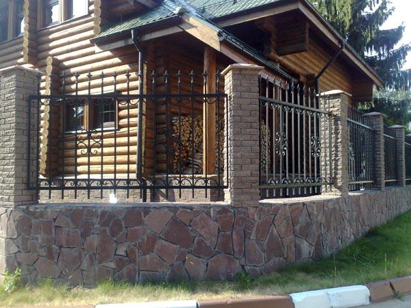 Кованый забор с бетонными столбами облицованными камнем